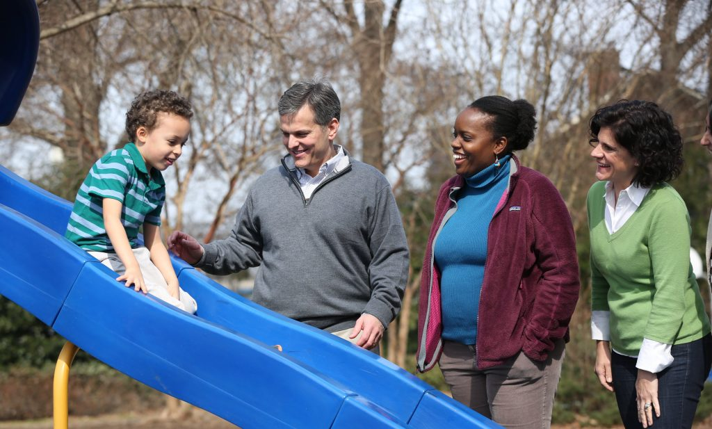 child sliding at playground while parent watch